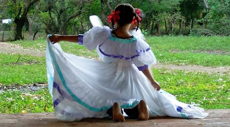 girl kneeling in white dancing dress, facing away