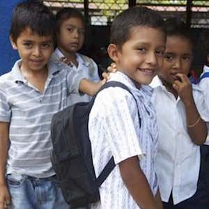 a group of primary school children, one is wearing a backpack