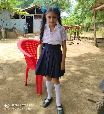 Young student dressed in the white shirt and navy skirt of a school uniform stands confidently outside her home.