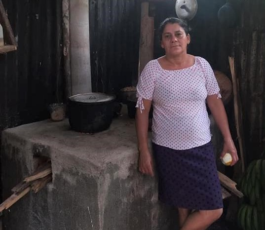 woman stands by a concrete stove; two pots sit on top; ends of firewood poke out of a hole on the side