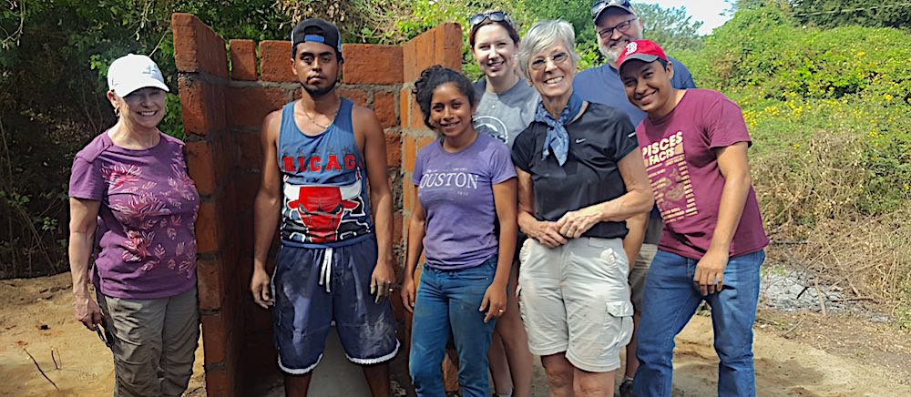 group of proud builders beside a mostly-finished latrine made of brick