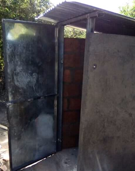 simple latrine or outhouse made of cinder block, metal roof, and metal door
