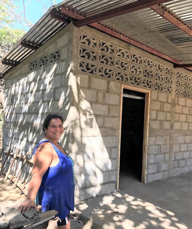 a smiling woman stands in front of a newly build house made of cinder blocks and a shiny metal roof