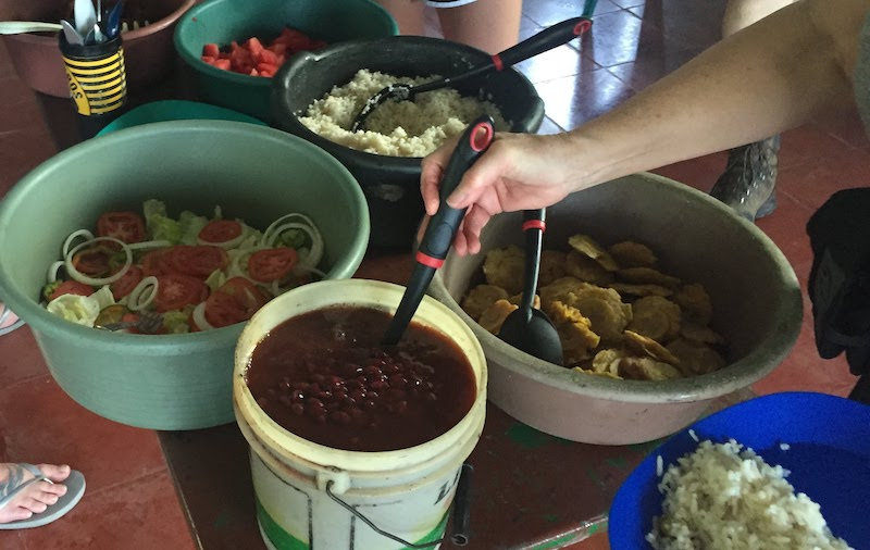 a spread of food including serving bowls of beans, rice, fried plantains, lettuce salad, and watermelon