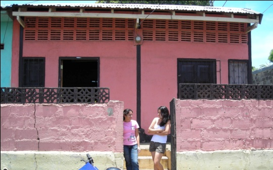 the front of Beca House with two young adult students standing in the gate