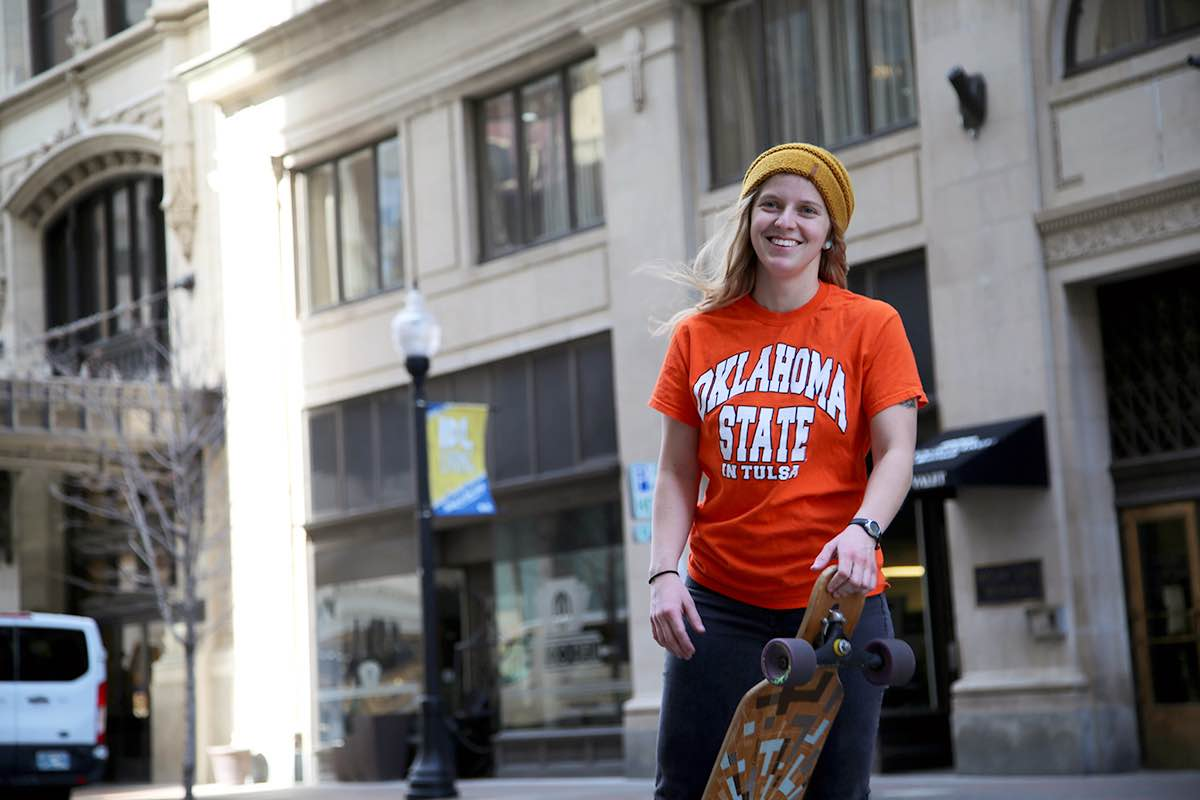 OSU-Tulsa student Rachel Millea in a staged photograph. She is holding a skateboard on a street in downtown Tulsa.