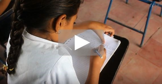 a girl sits at a school desk writing in a notebook