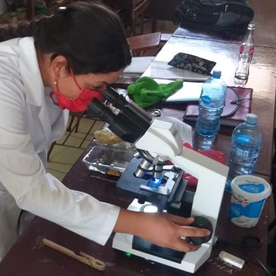 a woman dressed in a white lab coat looks through a microscope