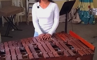 A young woman stands behind a marimba