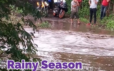 Several men, three with motorcycles, stand pondering the rushing water flowing along what should be a dirt road. The water is clearly swift, of unknown depth, and about 30 feet across.