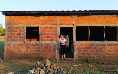A woman stands in the doorway of a damaged house