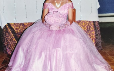 A young woman poses wearing a pink gown