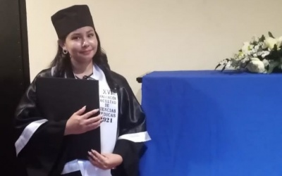 Valeria stands in an academic gown holding a diploma.